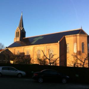 Zonnepanelen op kerk Haarlem. Zowel kruis als omliggende panelen op kerkdak zijn PV-panelen.